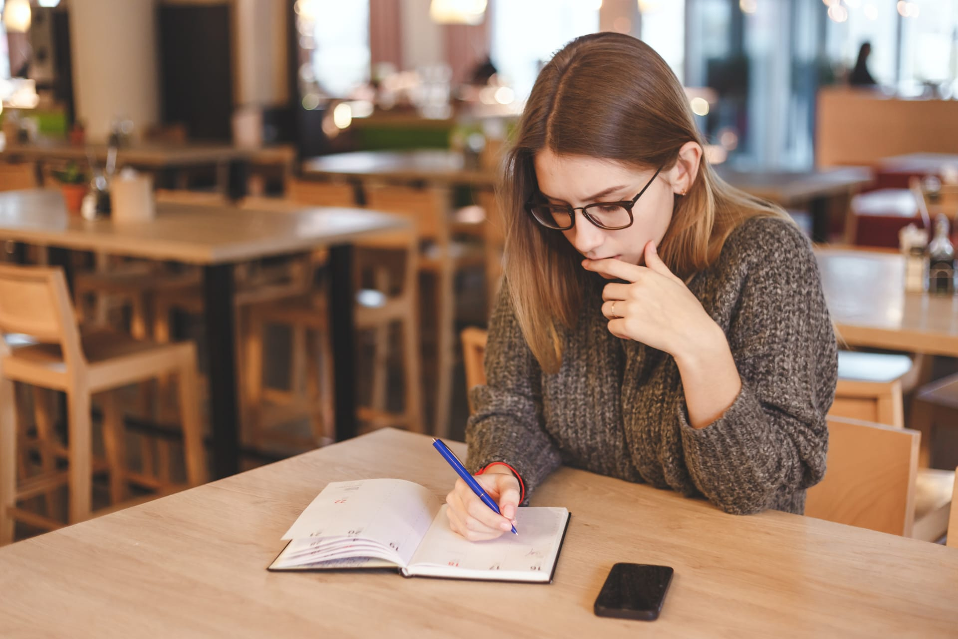 Girl writing in the notebook while sitting at a cafe