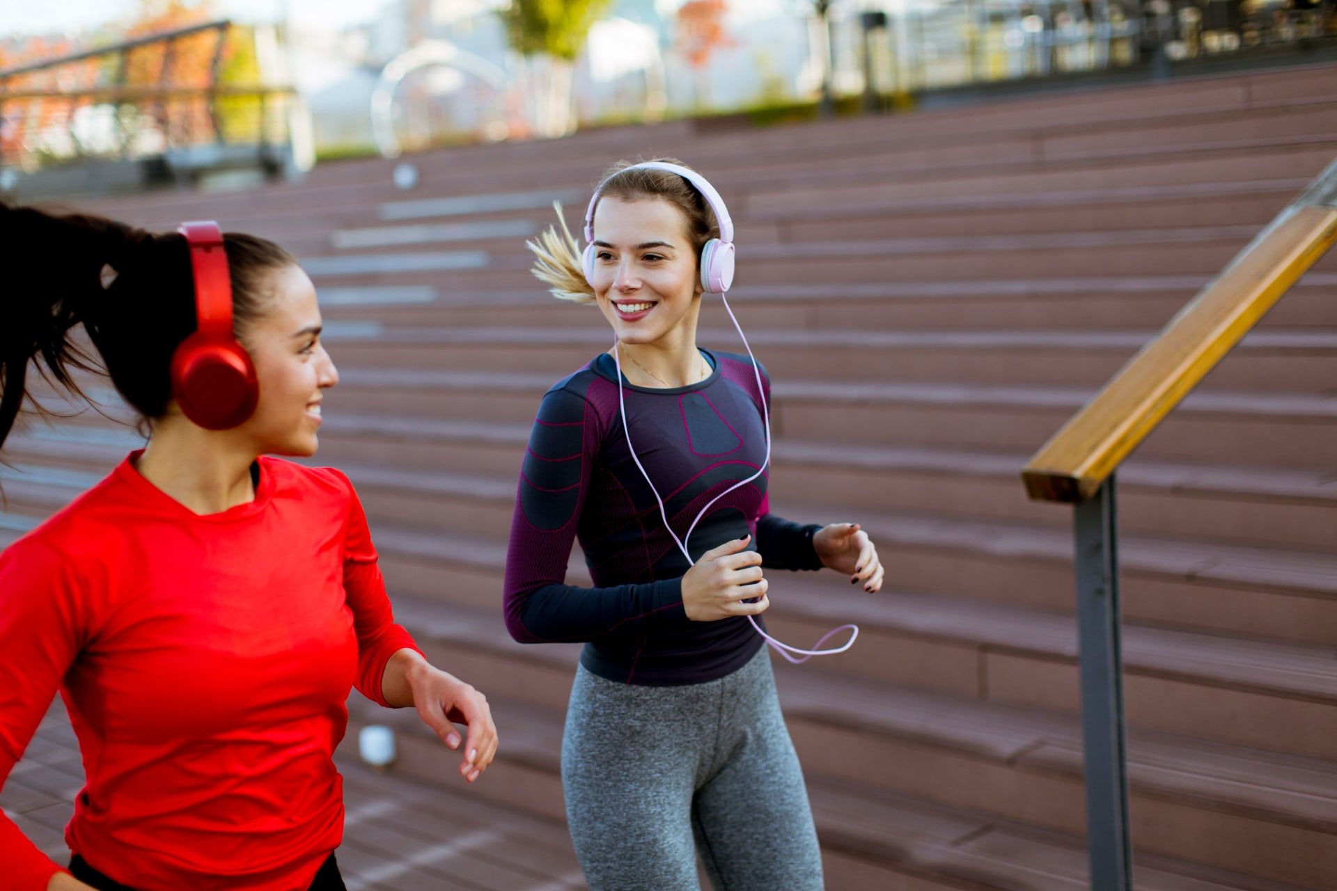 Girls running and listening to music on their headphones