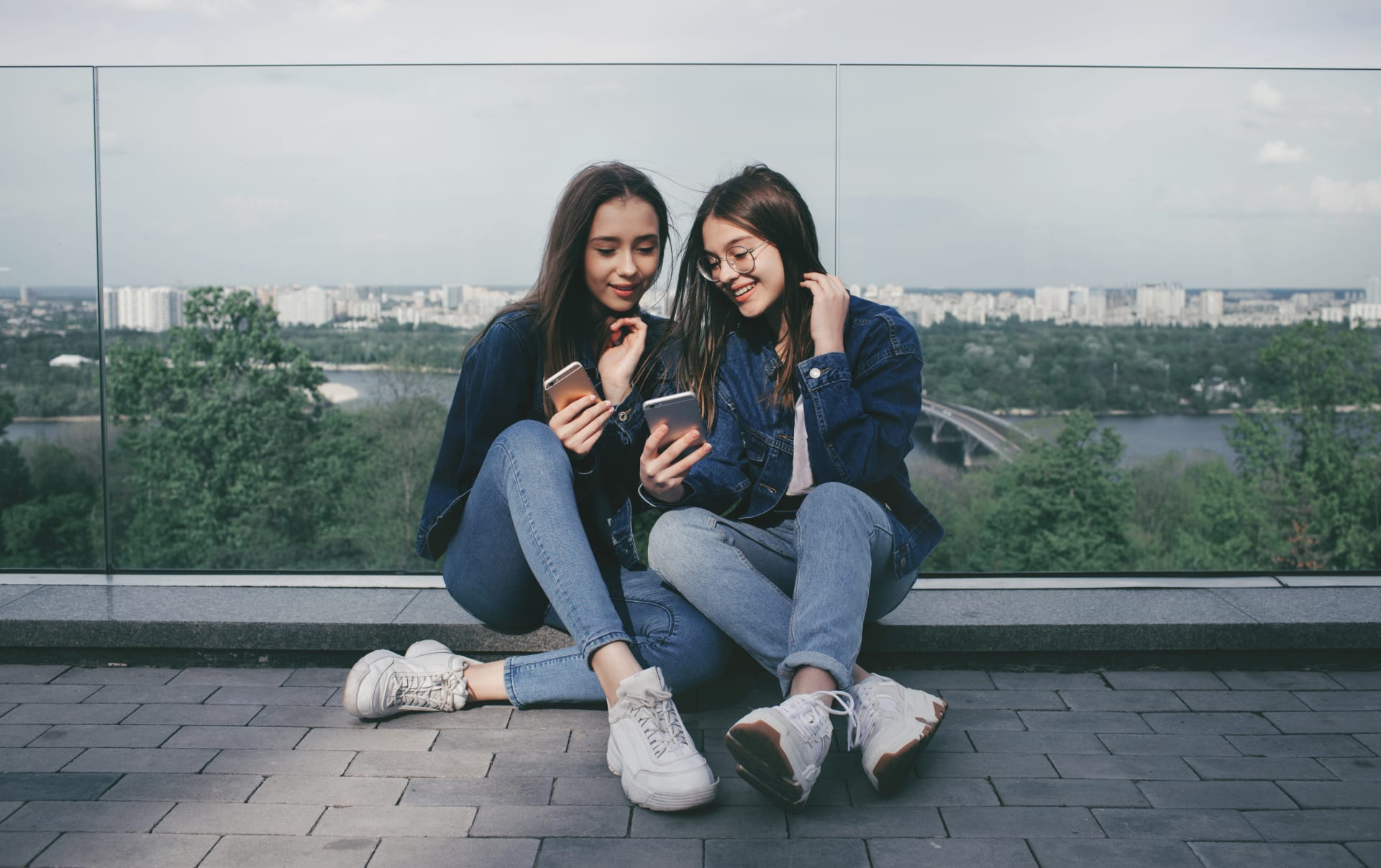 Girls sitting against a glass fence