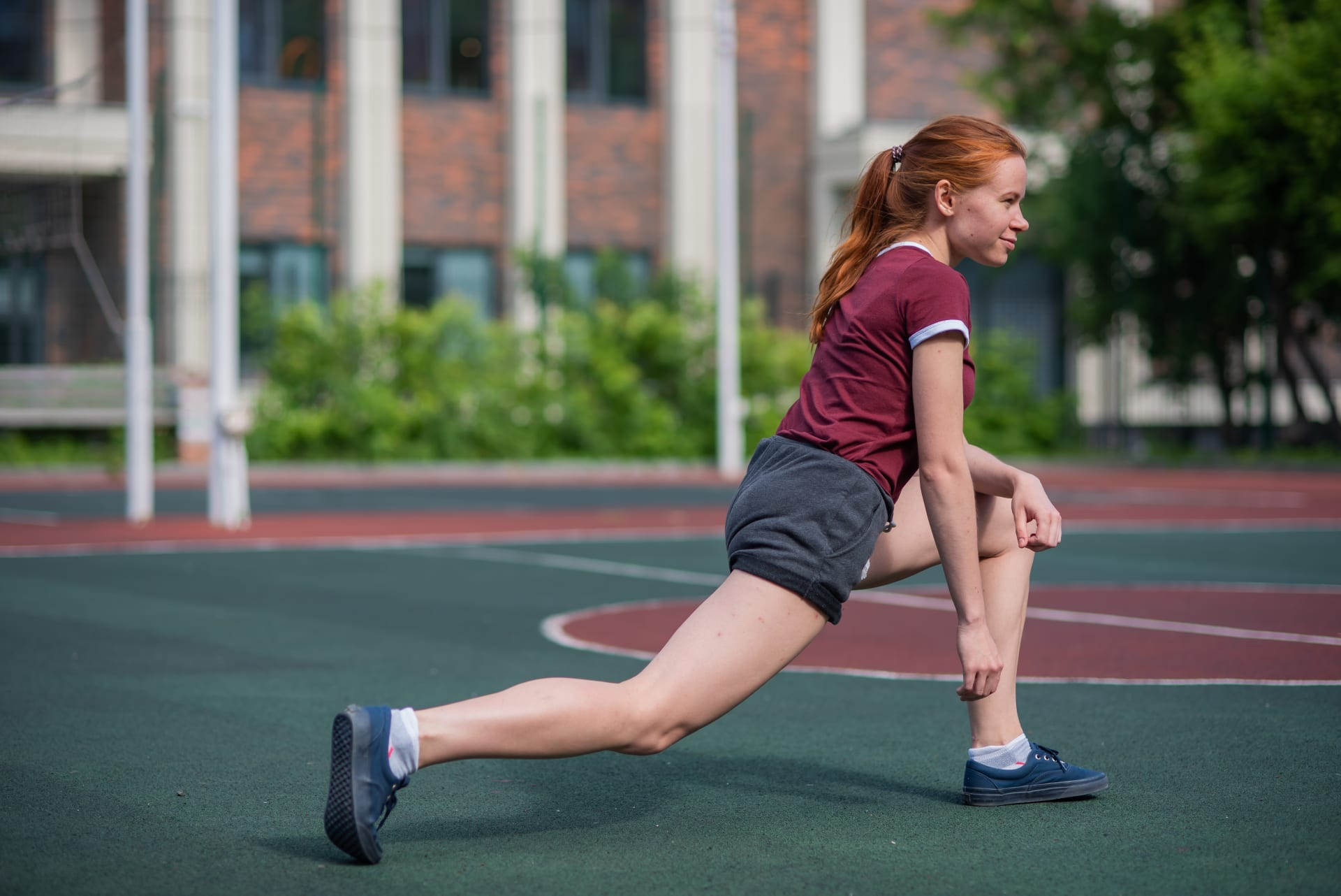 Girl in a lunge position on a basketball field