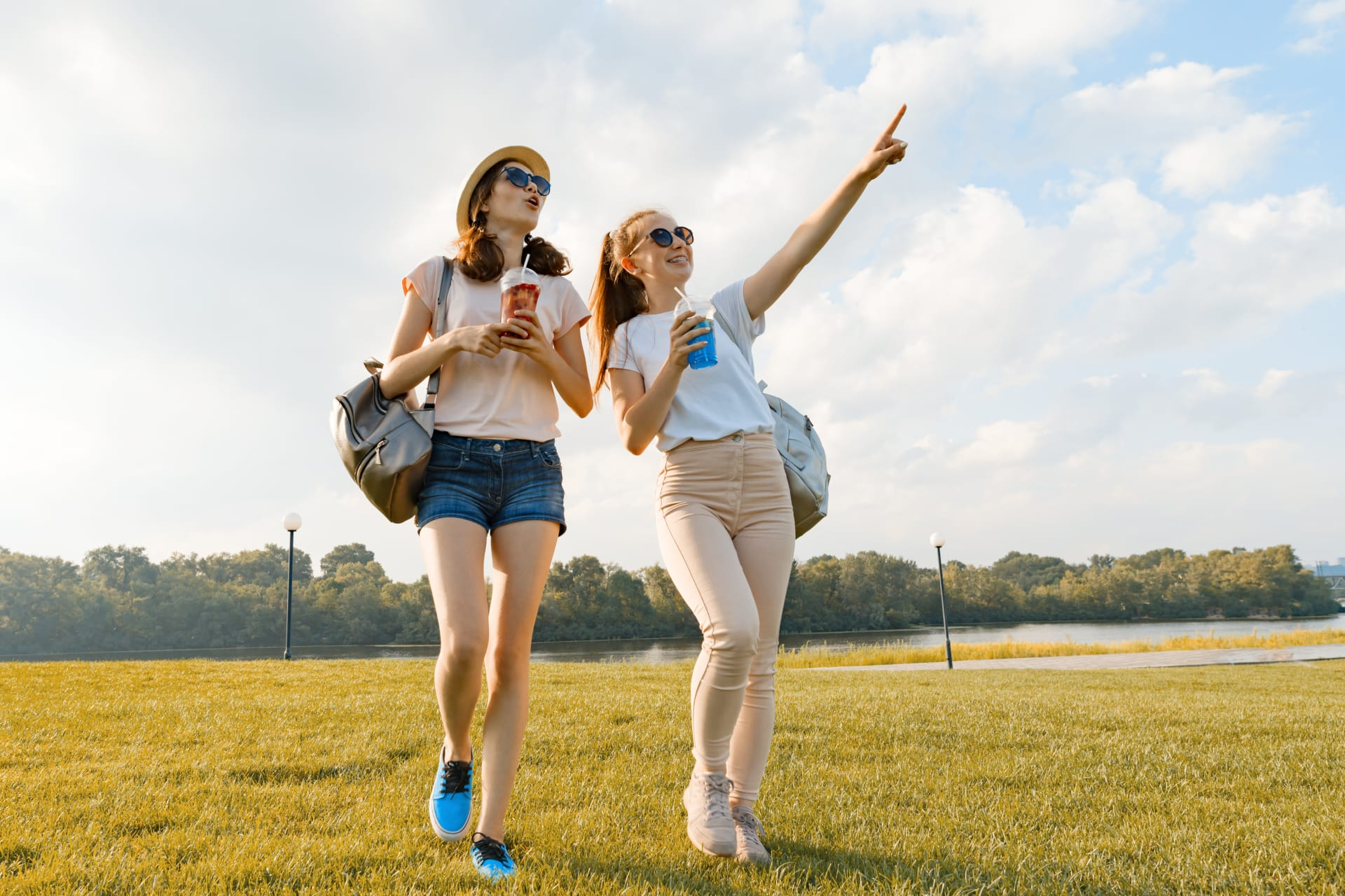 Girl pointing at the sky while walking with her friend in nature