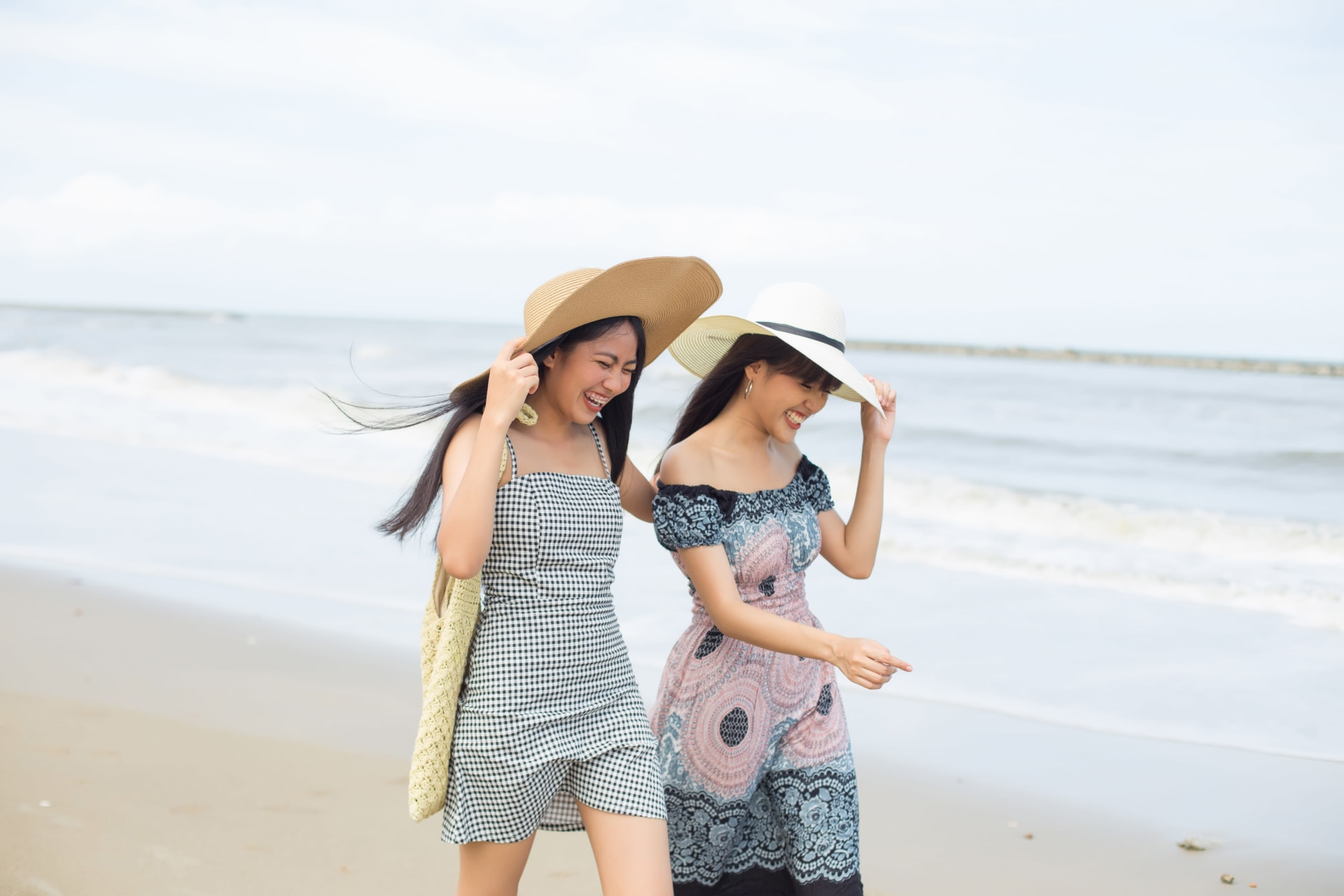 Two women laughing while holding their hats and walking on the beach