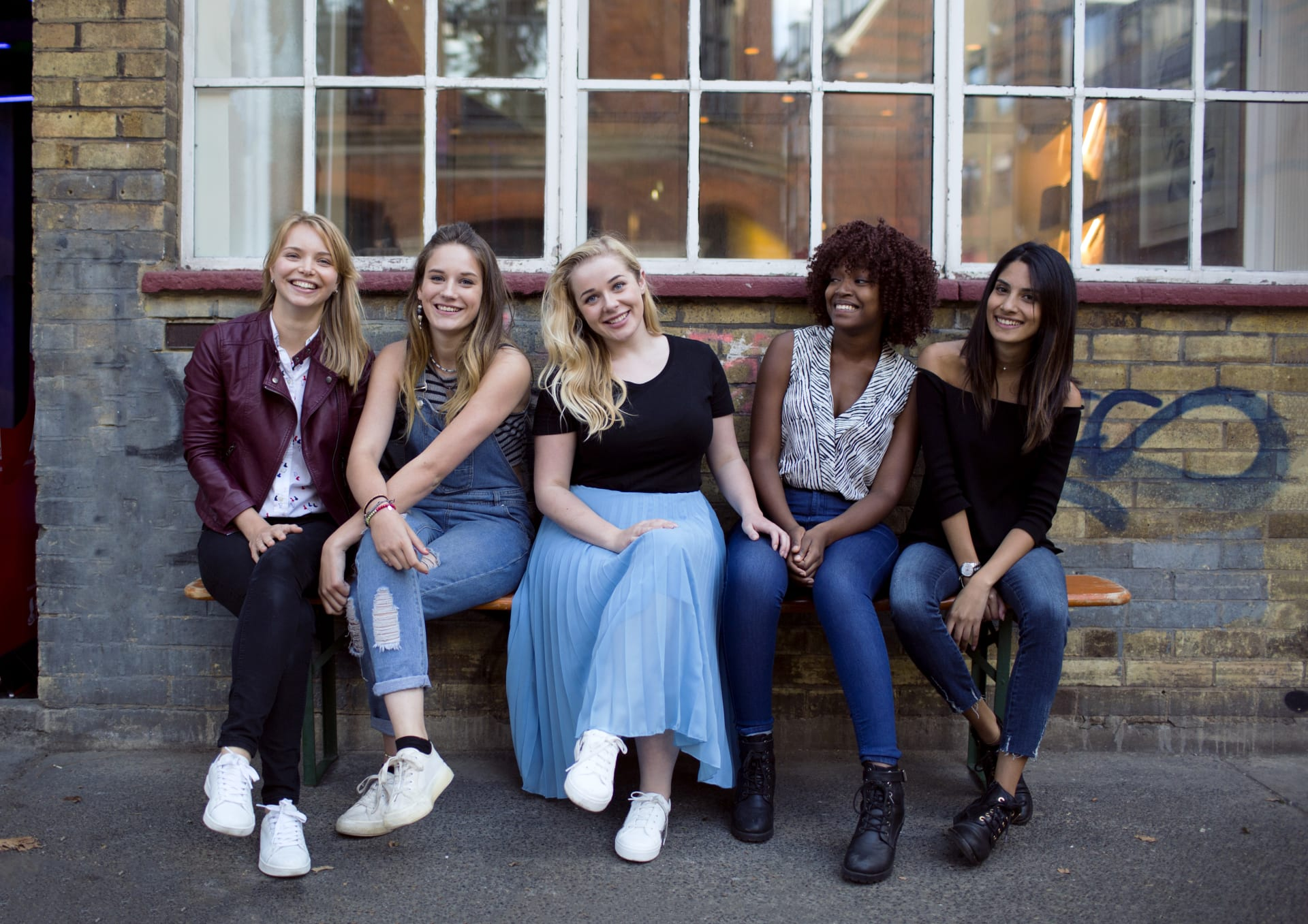 Girls sitting on a bench and smiling in front of a building
