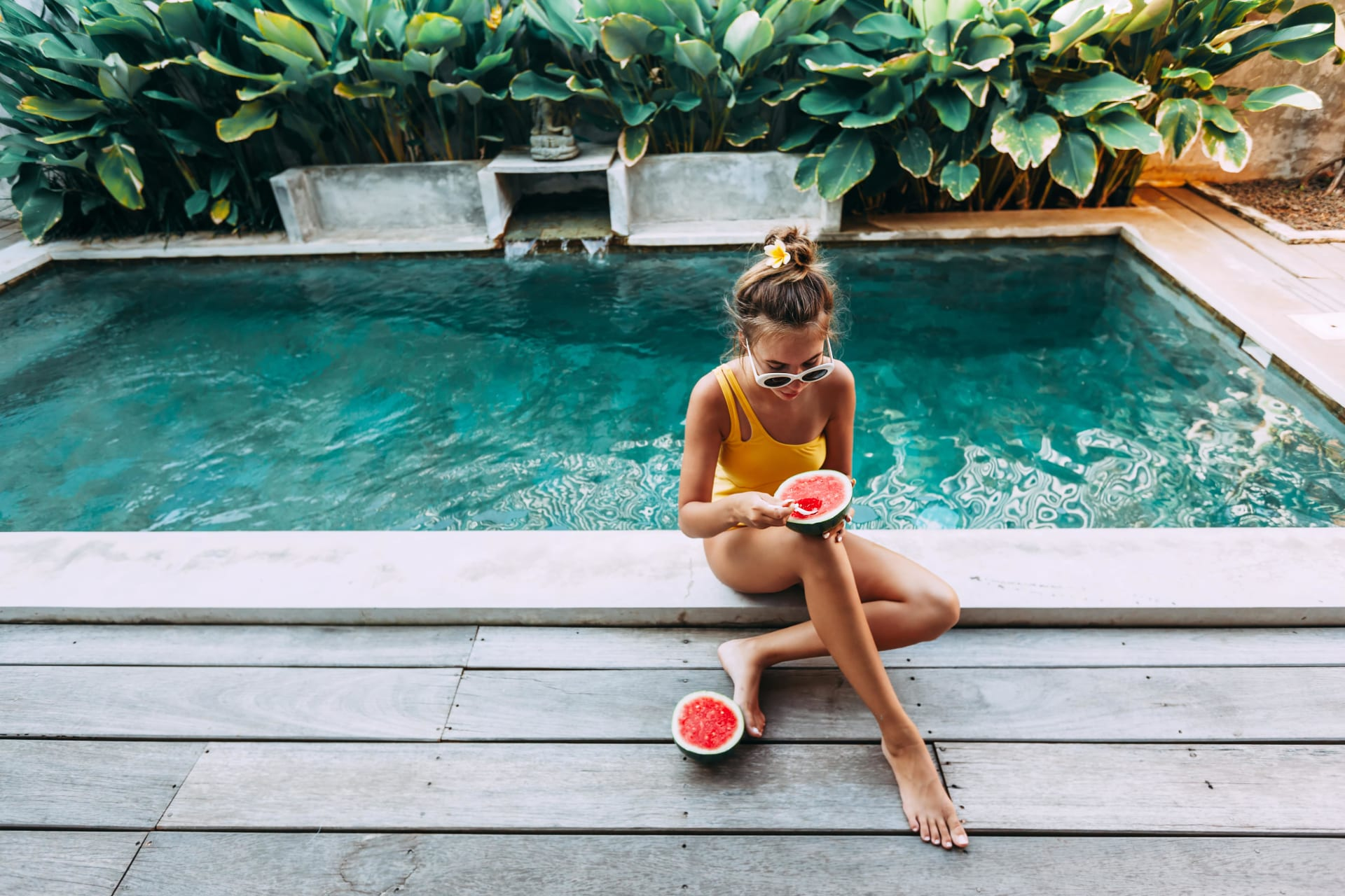 Girl eating a watermellon while sitting next to a pool