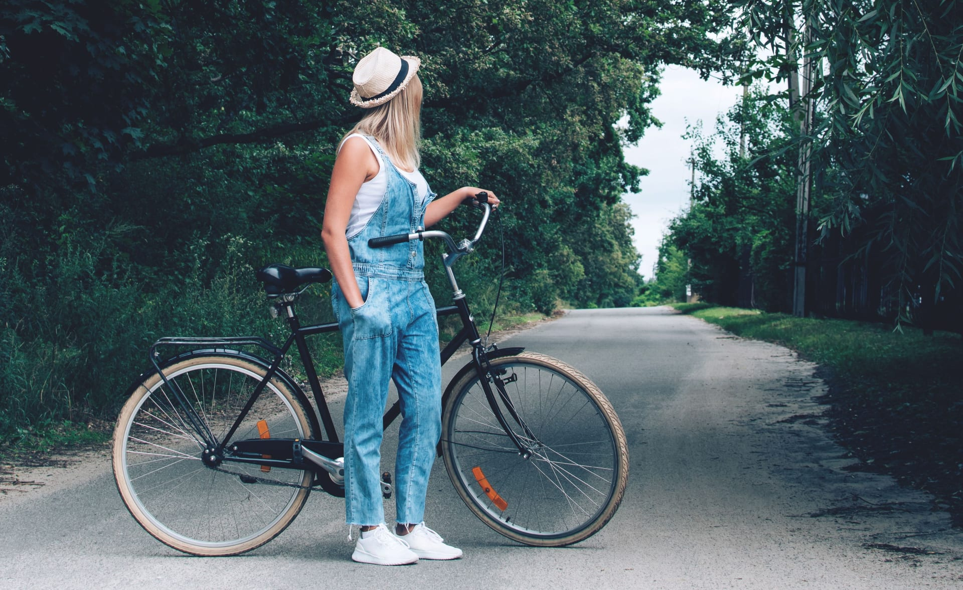 Woman standing with her bicycle on the road in the forest