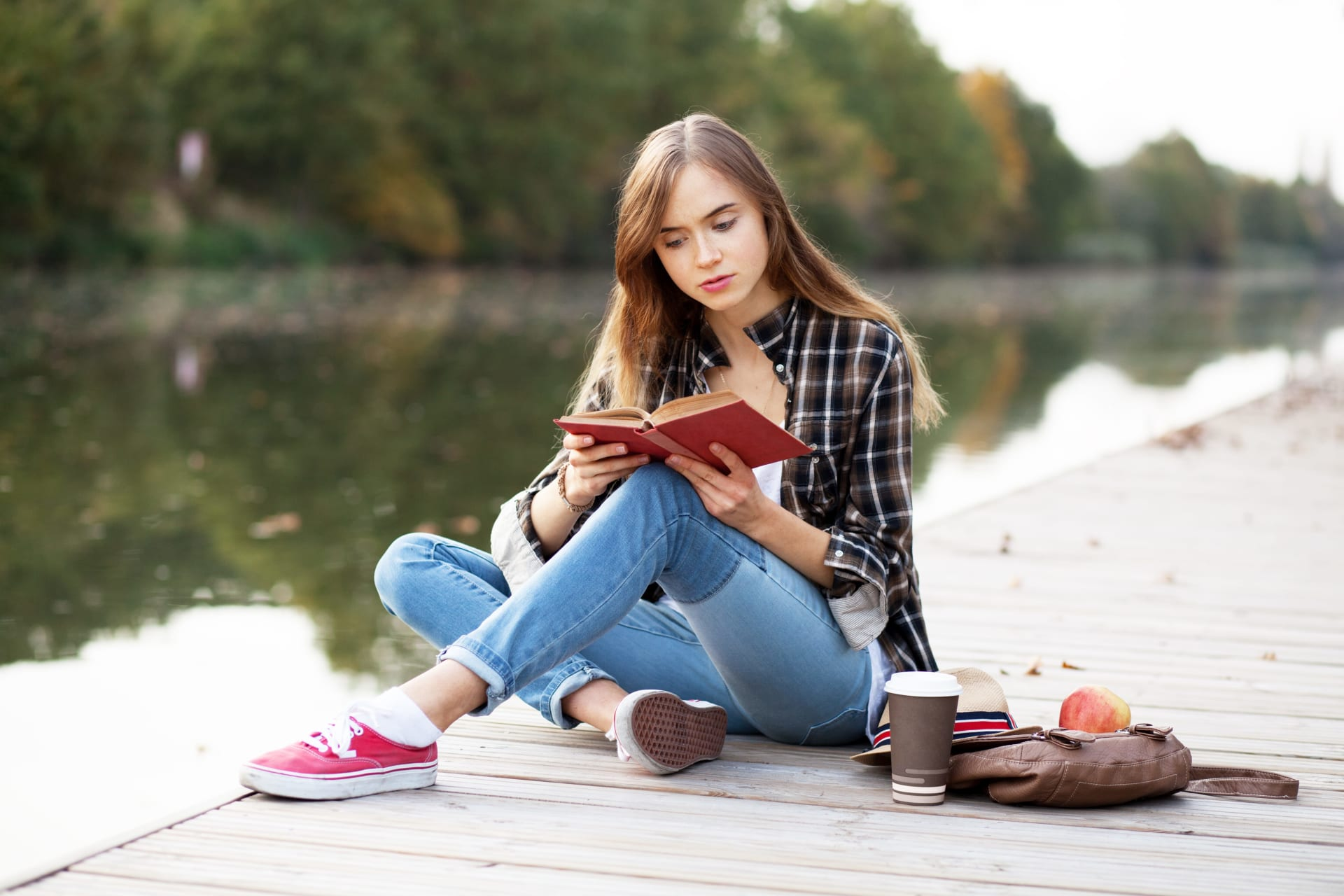 Girl reading a book while sitting on a dock