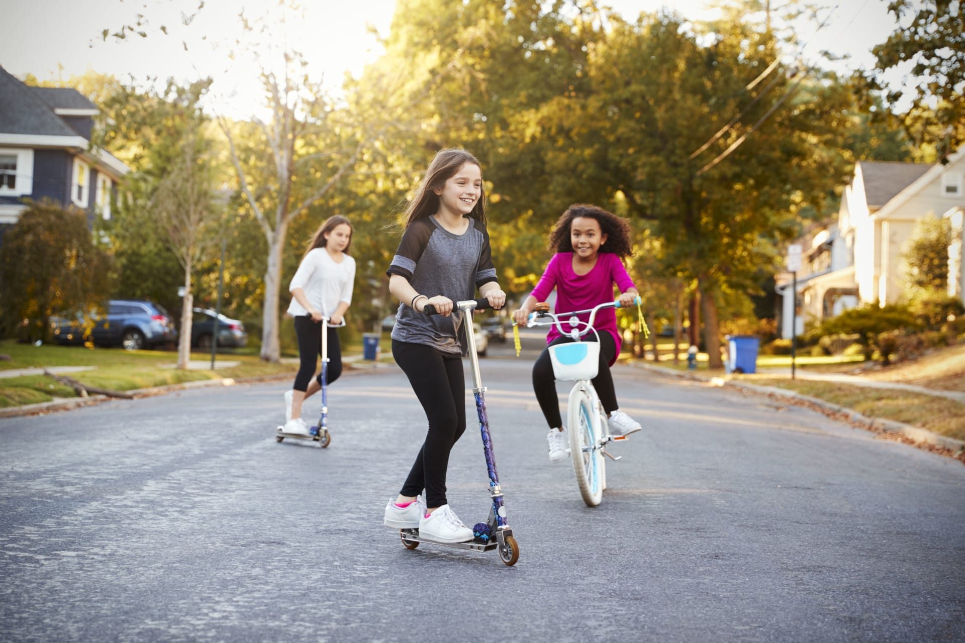 Young girls riding scooters and bicycles