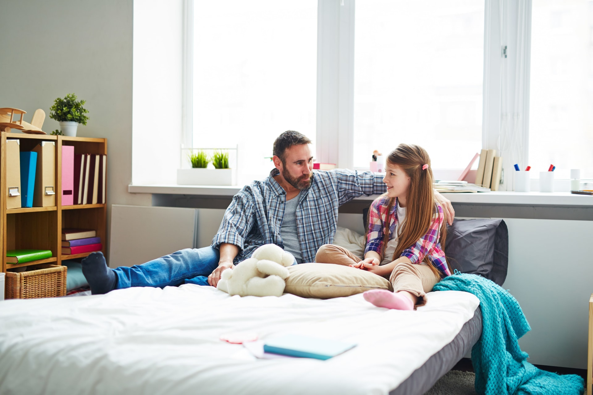 Father and daughter talking while sitting on a bed