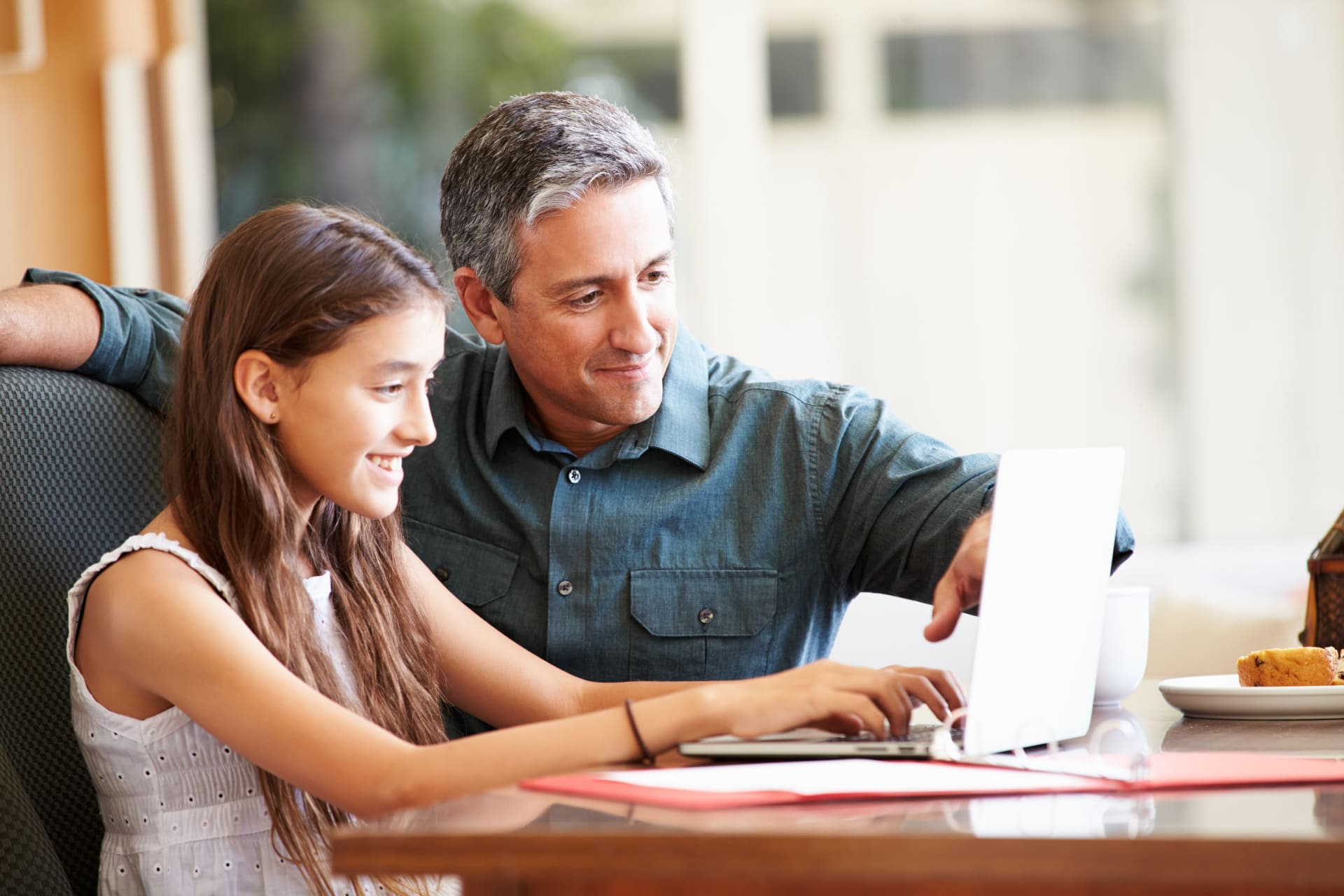 Daughter and father looking at a laptop screen