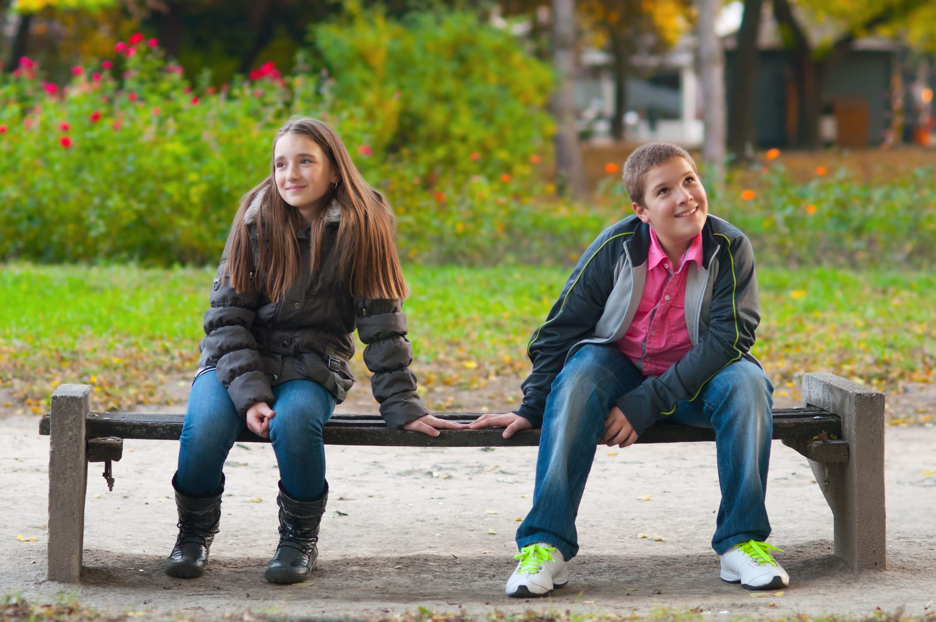 Girl and a boy sitting on a bench touching their hands while looking away
