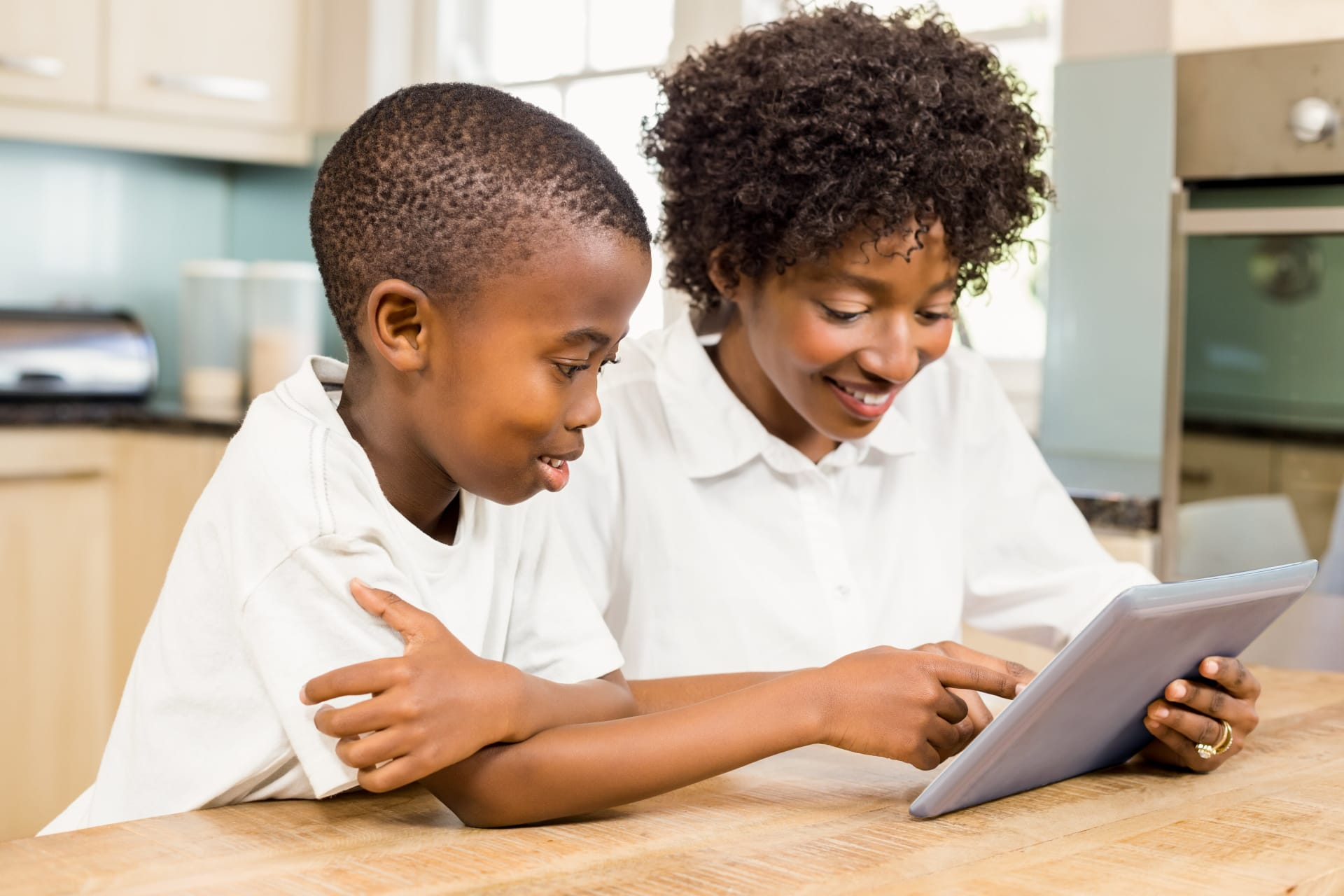 Son and mother holding a tablet