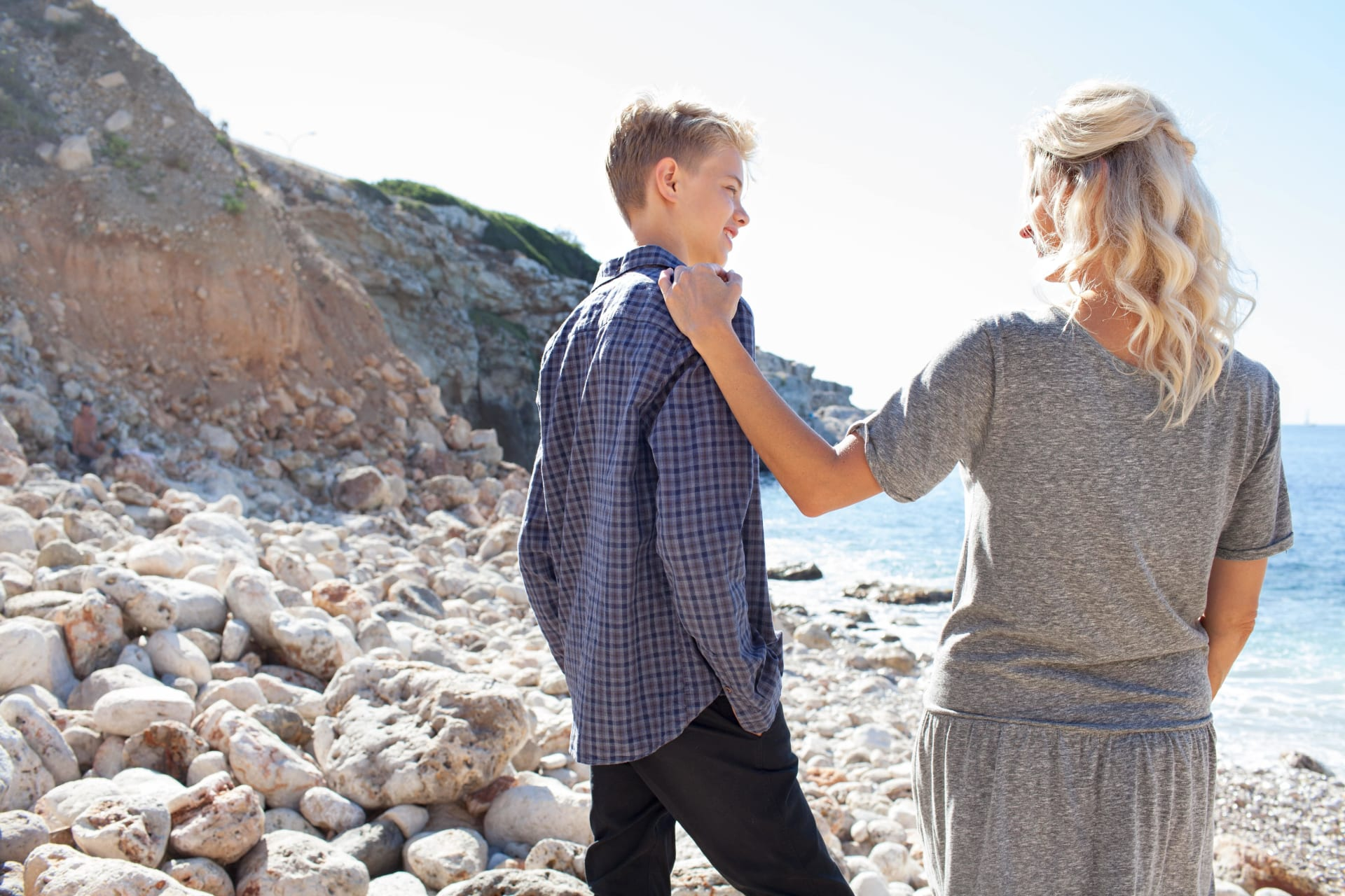 Mother and son standing on a beach