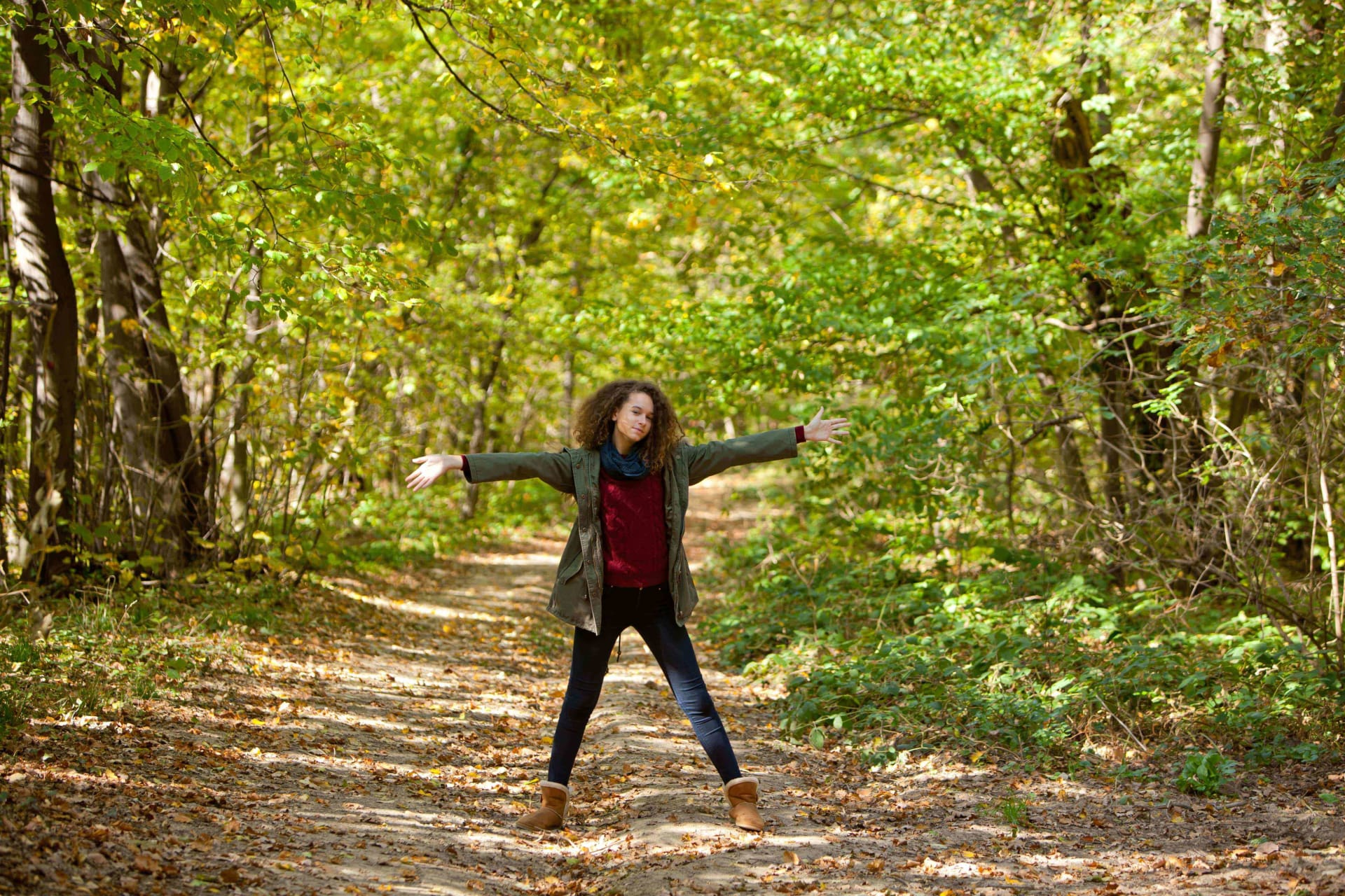 Woman standing in a autumn forest pathway with her arms wide open