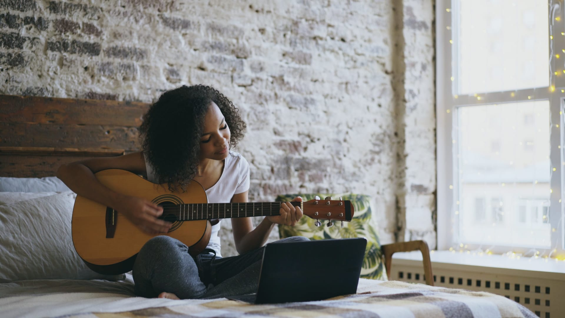 Girl playing a guitar while sitting on a bed