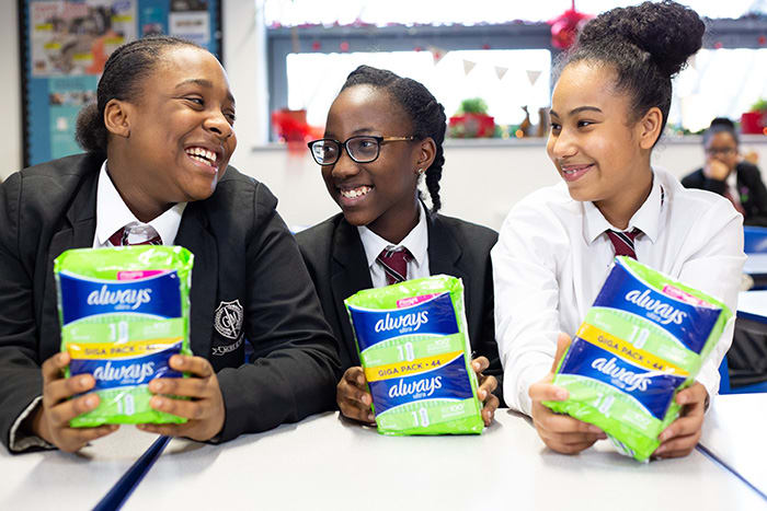Girls sitting at a desk and holding Always Sanitary Pads packaging