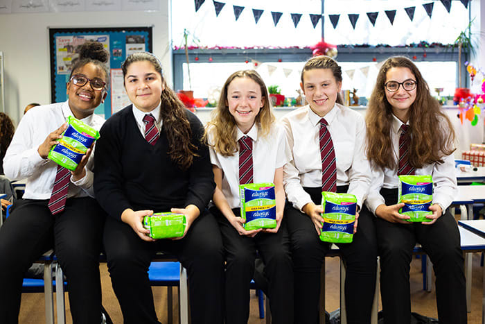 Girls standing and holding Always Sanitary Pads packaging