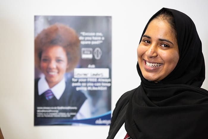 Portrait of a girl smiling standing in front of a End Period Poverty poster
