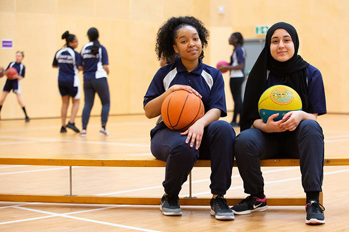 Girls sitting on a bench in basketball court