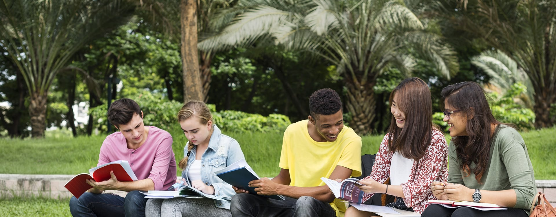 Teenagers sitting in the park while reading books