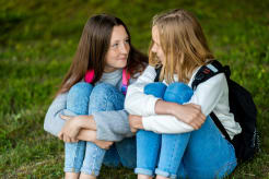 Two girls sitting on grass and looking each other