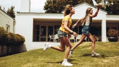 Two girls running and playing with airplane toy in backyard