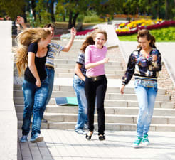 Girls running outside down the stairs and smiling