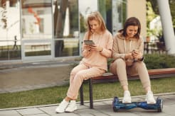 Two girls sitting on bench and looking at their phones
