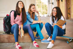 Girls sitting on a sidewalk and hanging out