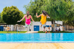 Two girls jumping into the pool