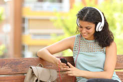 Girl sitting on a bench and listening to music on her phone