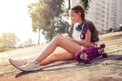 Girl sitting on a concrete floor with her skateboard