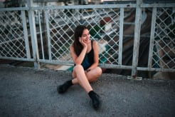 Girl sitting on a floor against a metal fence