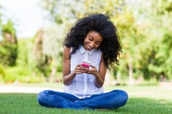 Girl sitting on grass and looking at her phone