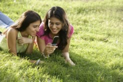 Two girls lying on grass and looking at a phone