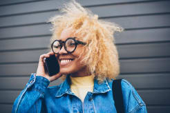 Portrait of a girl smiling while talking on her phone