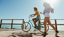 Woman riding a bike on the seashore and other woman walking next to her