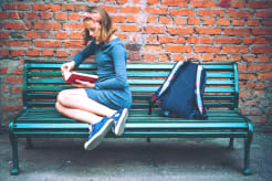 Girl sitting on a bench and reading a book