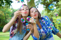 Two girls blowing bubles