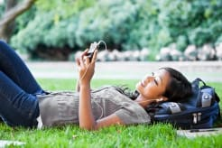 Girl lying on grass and looking at her phone