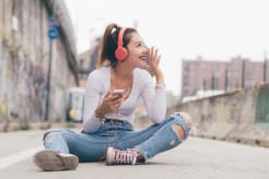 Girl sitting on the ground outside smiling and listening to music