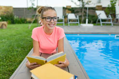 Girl lying next to a pool while holding a book and looking at the distance