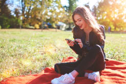 Girl looking at her phone while sitting on the grass