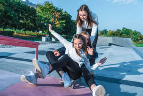 Girls sitting on a skateboard and riding it