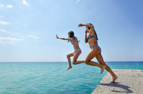 Two girls jumping into the sea