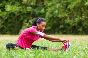 A girl stretching her leg while sitting in a field