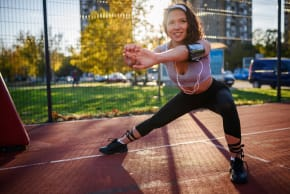 Girl doing a side squat at a running field during sunset