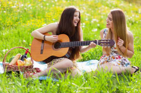 Two girls sitting in a field and playing a guitar