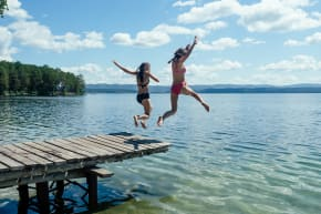 Two women jumping into a lake