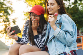 Two girls smiling while looking at a phone