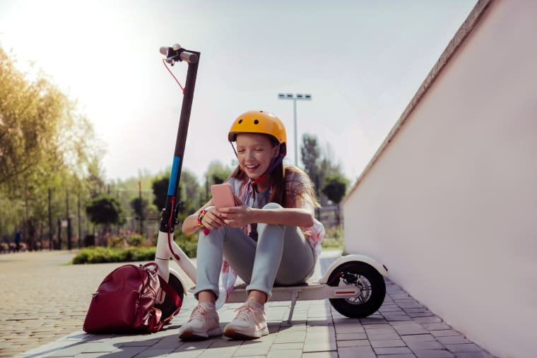 Girl sitting on a scooter and looking at her phone